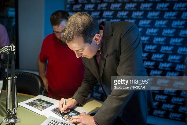 Sprint Cup Champion Kyle Busch autographs a picture for a fan after an interview with Mistress Carrie on WAAFFM on August 31 2016 in Boston...
