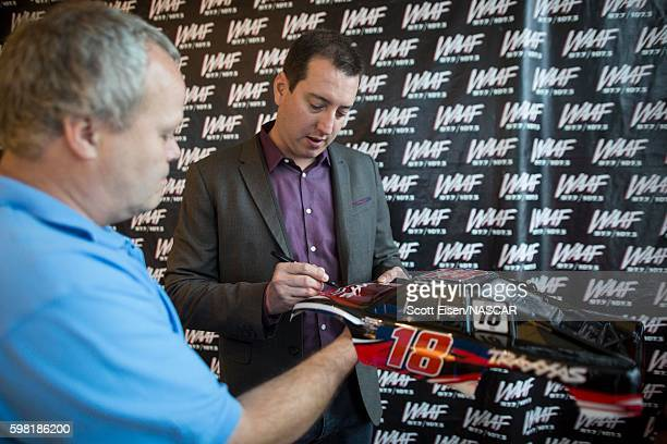 Sprint Cup Champion Kyle Busch autographs a shell of a remote control car after an interview with Mistress Carrie on WAAFFM on August 31 2016 in...