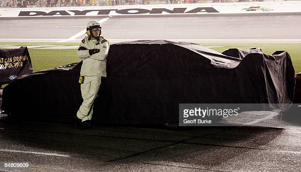 Sprint Cup official stands next to a car during a rain delay in the NASCAR Sprint Cup Series Daytona 500 at Daytona International Speedway on...