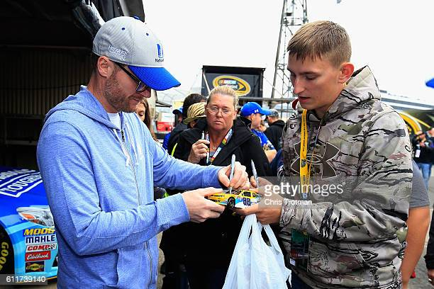 Sprint Cup Series driver Dale Earnhardt Jr signs autographs for fans during practice for the NASCAR Sprint Cup Series Citizen Solider 400 at Dover...