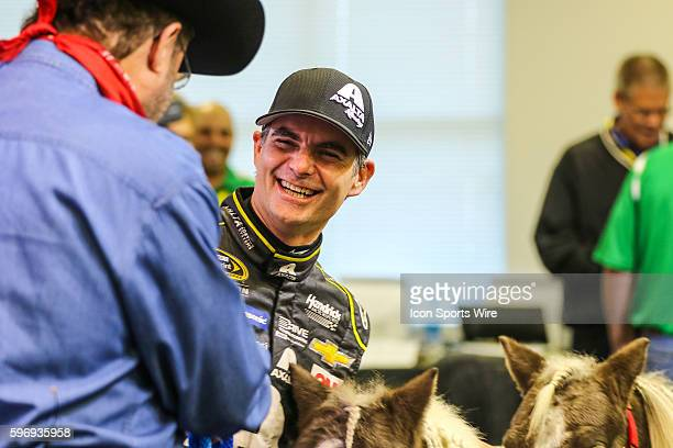 Sprint Cup Series driver Jeff Gordon smiles and laughs when Texas Motor Speedway President Eddie Gossage presents him with two ponies as a retirement...