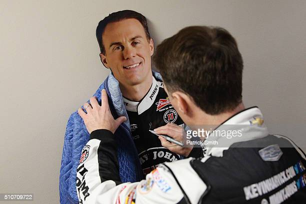 Sprint Cup Series driver Kevin Harvick signs a cardboard cutout of himself during NASCAR Media Day at Daytona International Speedway on February 16...