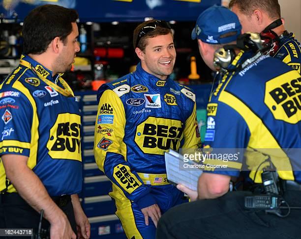Sprint Cup Series driver Ricky Stenhouse Jr center talks with crew members following practice at Daytona International Speedway in Daytona Beach...