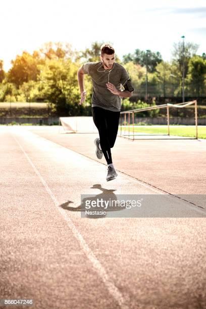 Sprinter running against sun on running track