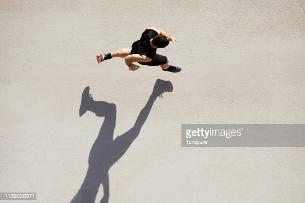 sprinter seen from above with shadow and copy space. - running stock pictures, royalty-free photos & images