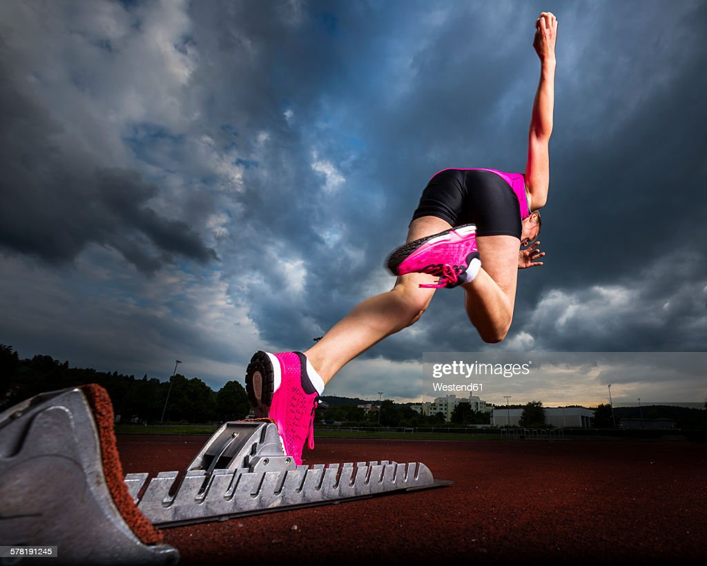 Sprinter starting under cloudy sky : Stock Photo