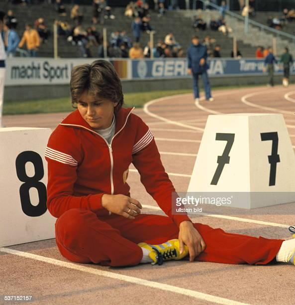 Sprinterin DDR sitzt vor einem Startblock vor einem Wettkampf und macht sich warm oJ