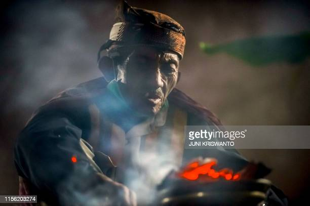 A spriritual leader prays as Tengger tribe members and local tourists climb the summit of Mount Bromo volcano to throw offerings from the summit or...