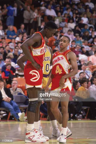 Spud Webb of the Atlanta Hawks listens to teammate Dominique Wilkins during a NBA game against the Los Angeles Lakers at the Great Western Forum in...