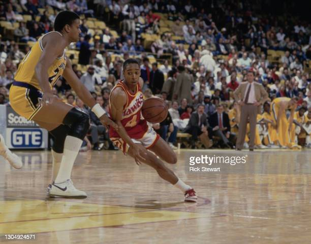 Spud Webb, Point Guard for the Atlanta Hawks dribbles the basketball past Maurice Lucas, Power Forward of the Los Angeles Lakers during their NBA...