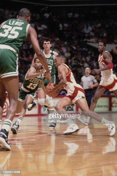 Spud Webb#4, Point Guard for the Atlanta Hawks dribbles the basketball past Charles Smith of the Boston Celtics during their NBA Central Division...