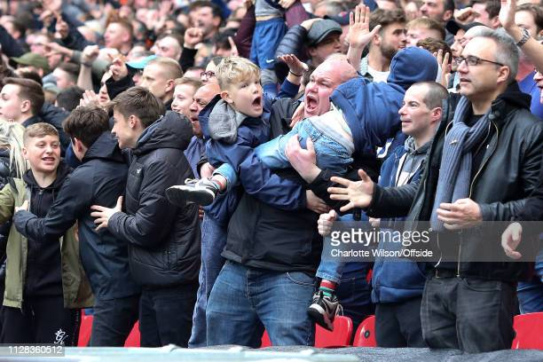 Spurs fan throws his sons over either shoulder as they celebrate a goal though it is later ruled offside during the Premier League match between...