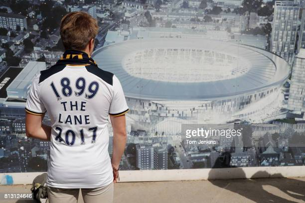 A Spurs fan wearing a shirt with dates of the old stadium looks at an image of the new stadium before the Tottenham Hotspur v Manchester United FA...