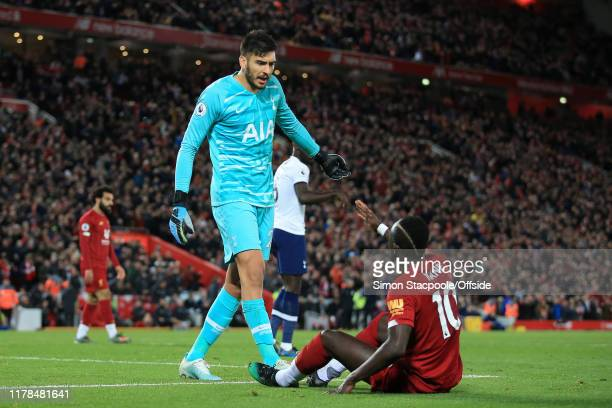 Spurs goalkeeper Paulo Gazzaniga questions Sadio Mane of Liverpool after the striker won a penalty during the Premier League match between Liverpool...