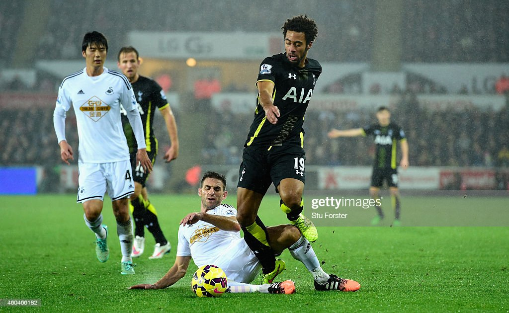Spurs player Mousa Dembele (r) is tackled by Angel Rangel during the Barclays Premier League match between Swansea City and Tottenham Hotspur at Liberty Stadium on December 14, 2014 in Swansea, Wales.