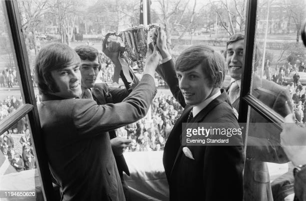 Spurs players from left Peter Collins Pat Jennings Martin Peters and Martin Chivers stand together on a balcony holding the English football League...