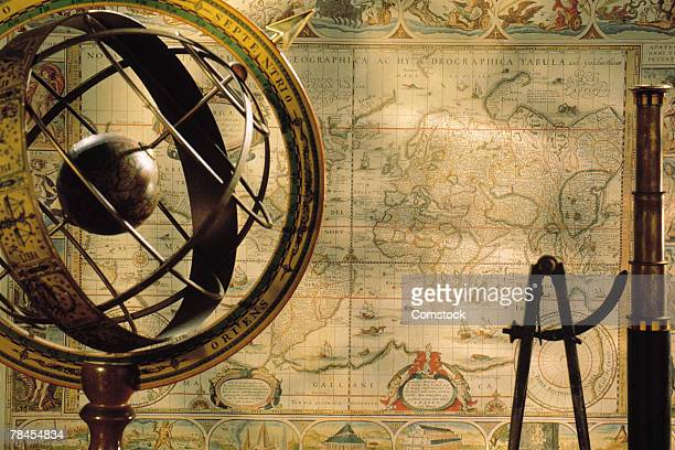 spyglass and compass with old map and globe
