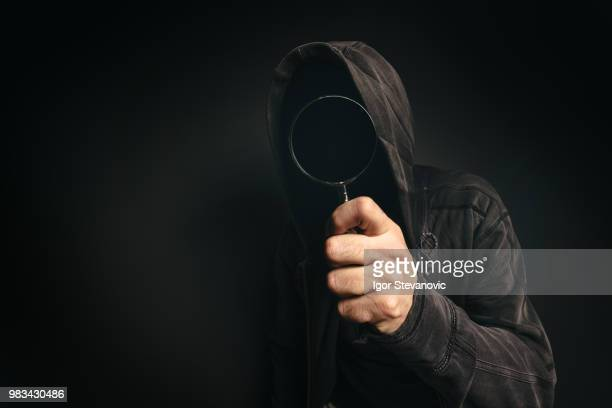 spyware computer software, hooded spooky person with magnifying - android malware stock pictures, royalty-free photos & images