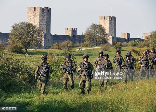 A squad from Skaraborg Armoured Regiment patrol outside Visby's 13th century city wall in Sweden on September 14 2016 Sweden's Baltic Sea island of...