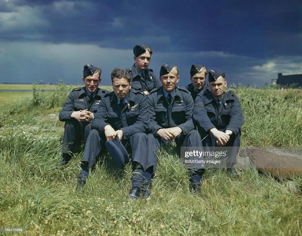 617 Squadron (Dambusters) At Scampton, Lincolnshire, 22 July 1943, The crew of Lancaster ED285/`AJ-T' sitting on the grass, posed under stormy clouds. Left to right: Sergeant G Johnson; Pilot Officer D A MacLean, navigator; Flight Lieutenant J C McCarthy, pilot; Sergeant L Eaton, gunner. In the rear are Sergeant R Batson, gunner; and Sergeant W G Ratcliffe, engineer, 22 July 1943.