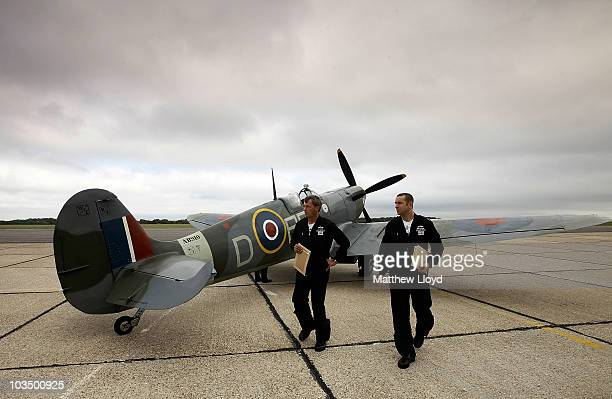 Squadron Leader Al Pinner and Squadron Leader Duncan Mason of the RAF walk past a Spitfire Mk Vb from the Battle of Britain Memorial Flight at Biggin...