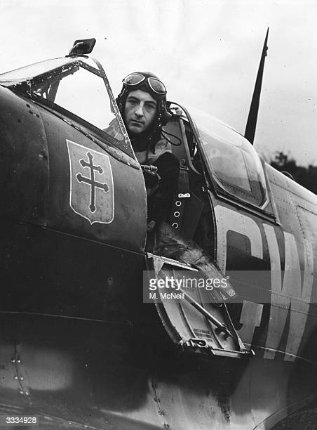 Squadron Leader Bernard Duperier of the No 340 'Ile-de-France' Free French Squadron, Royal Air Force sits in the cockpit of his Spitfire IXB,...