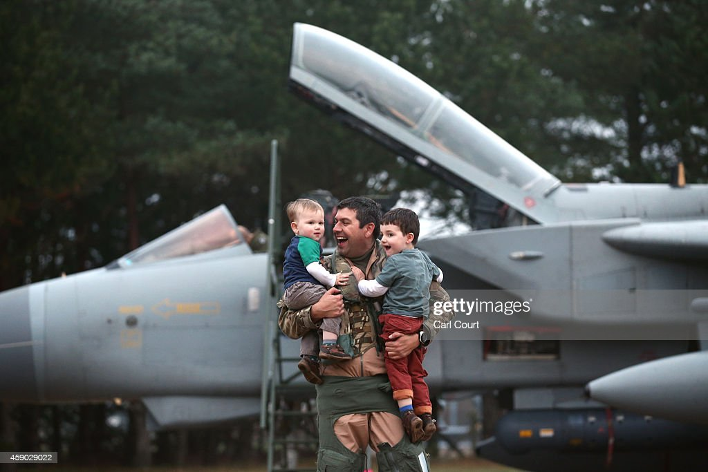 Squadron leader Gareth Prendergast holds his sons, Hector, 3, and Felix, 1, upon arriving on a Royal Air Force Tornado GR4s at Royal Air Force (RAF) Marham on November 15, 2014 near the village of Marham in the English county of Norfolk, England. The air crew departed their stopover at RAF Akrotiri, Cyprus early this morning after the jets from 31 Squadron left Kandahar airfield in Afghanistan on November 11 after following more than five years in the country.