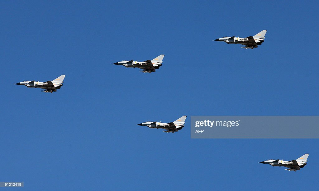 A squadron of Chinese Jian-series fighter jets executes a fly-by in