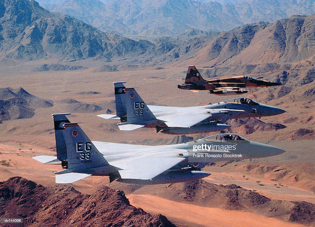 Squadron of military airplanes over desert mountains : Stock Photo