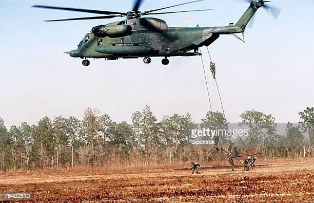 Squadron rappelling from helicopter