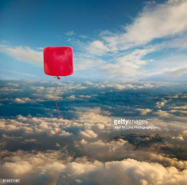 Square balloon floating over clouds