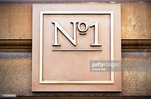 Square brass house number with 'No 1' copy space, vignette