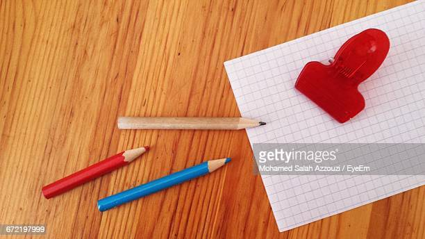 Square Line Paper With Paper Clip And Pencils On Table