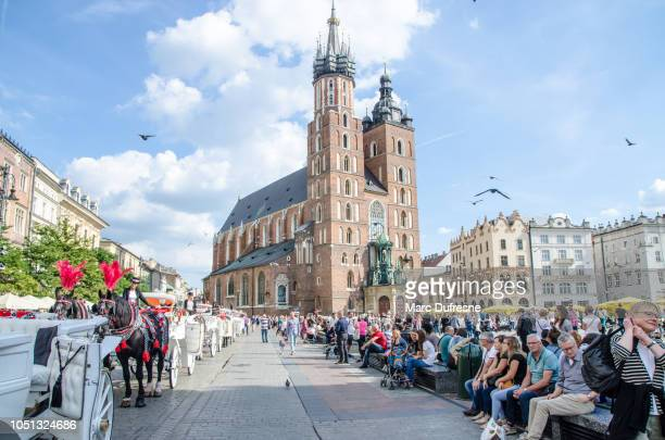 Square Market downtown Krakow with St-Mary Basilica behind and crowd during summer day
