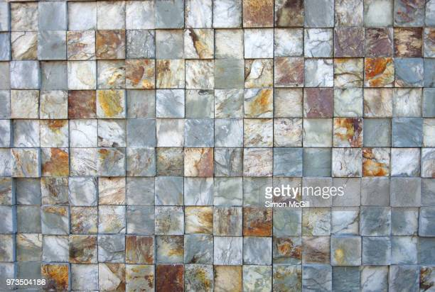Square natural stone mosaic tiles on a building exterior wall
