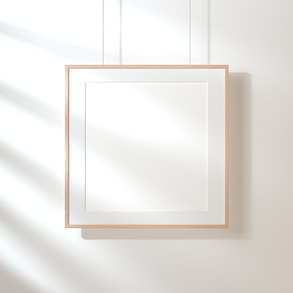Square poster with wooden frame mockup hanging on the wall with shadows 870402918
