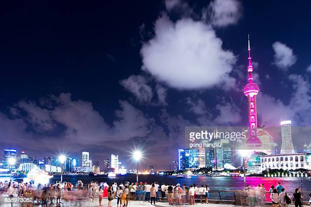 square with crowded people near illuminated tower in night shanghai