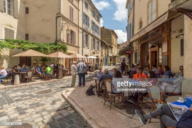 carré avec les touristes assis sur les terrasses à lourmarin, provence, france - village photos et images de collection