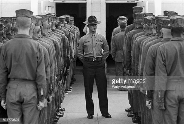 A squaredaway Marine drill instructor wearing the fabled campaign hat inspects his charges closely as they line up to go into a mess hall for chow...