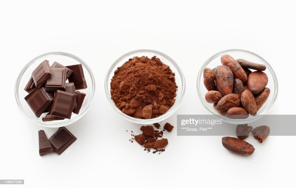 Squares of chocolate, cocoa powder and cocoa beans in glass dishes : Stock Photo