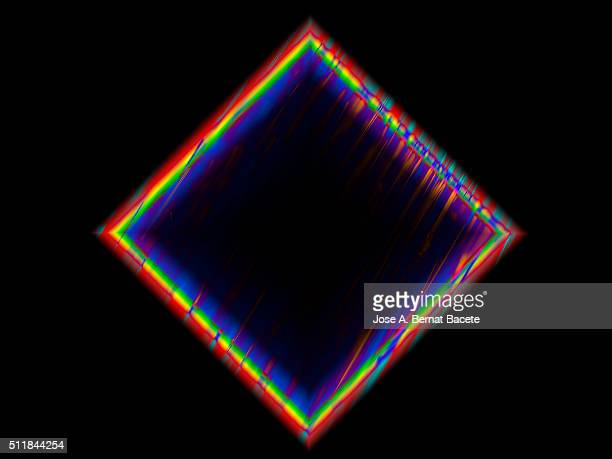 Squares of concentric colors on a black bottom of water drops