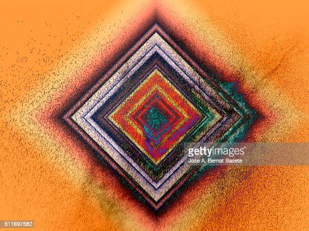 Squares of concentric colors on a orange bottom of water drops