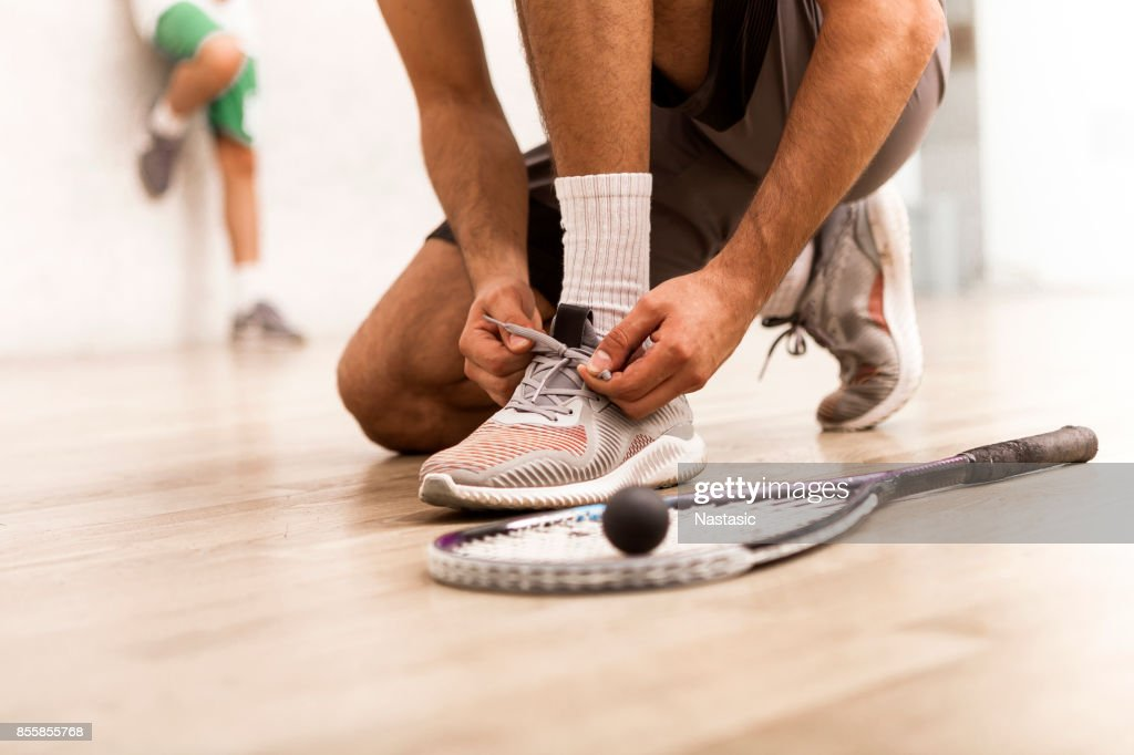 Squash player tying shoelaces : Stock Photo