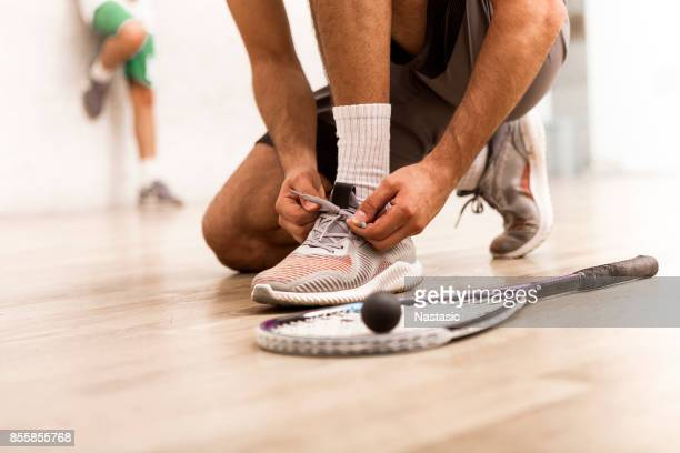 Squash player tying shoelaces