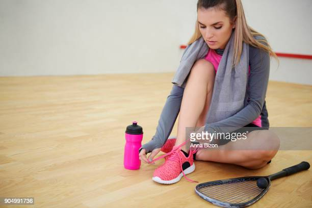 squash player tying sports shoe. debica, poland - racquet stock pictures, royalty-free photos & images