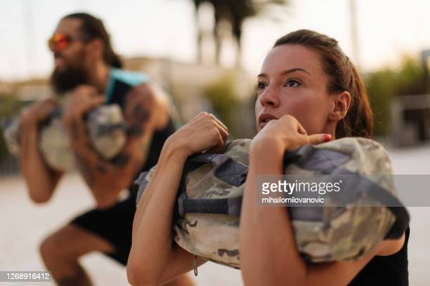 squatting with sandbags was never easy - sandbag stock pictures, royalty-free photos & images