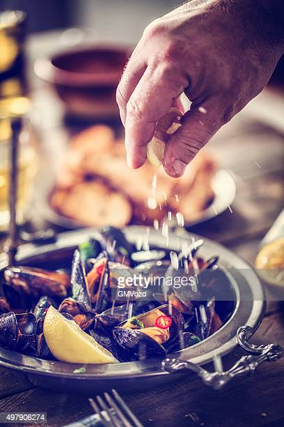 Squeezing Lemon on Classic French Mussels Dish