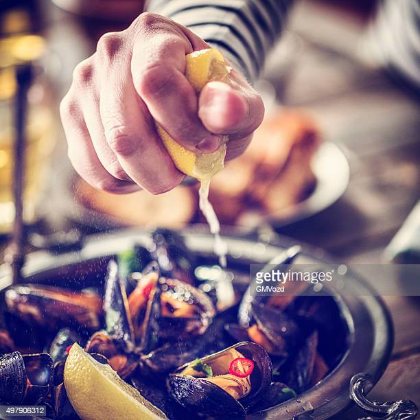 squeezing lemon on classic french mussels dish - seafood stock pictures, royalty-free photos & images