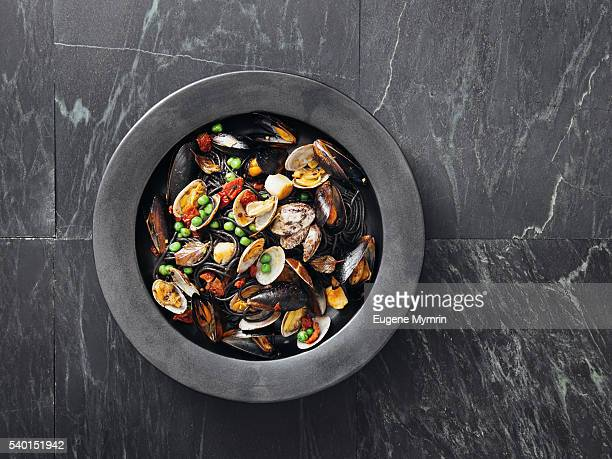 squid ink pasta with seafood and vegetables - seafood stock pictures, royalty-free photos & images