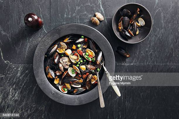 squid ink pasta with seafood and vegetables - mussel stock pictures, royalty-free photos & images
